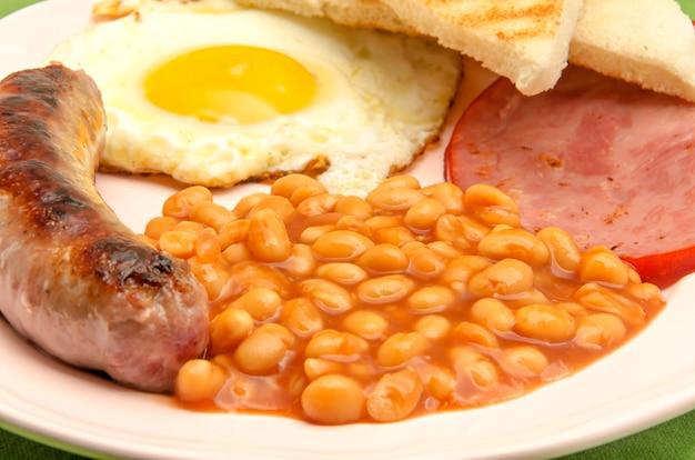 Desayuno inglés con frijoles, salchichas y huevo frito.