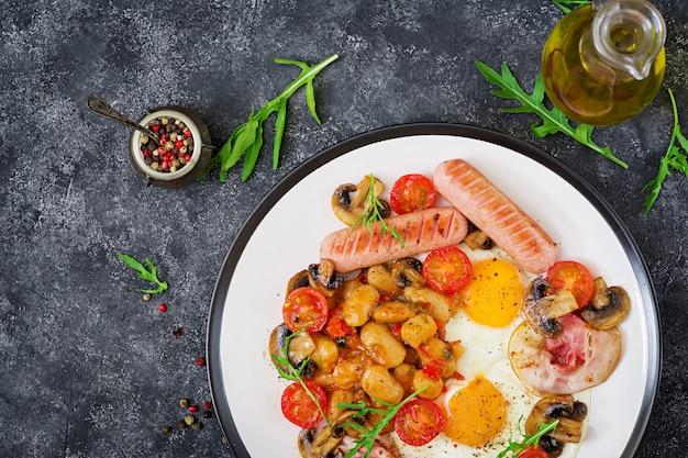 Desayuno inglés: huevo frito, frijoles, tomates, champiñones, tocino y salchichas. comida sabrosa.