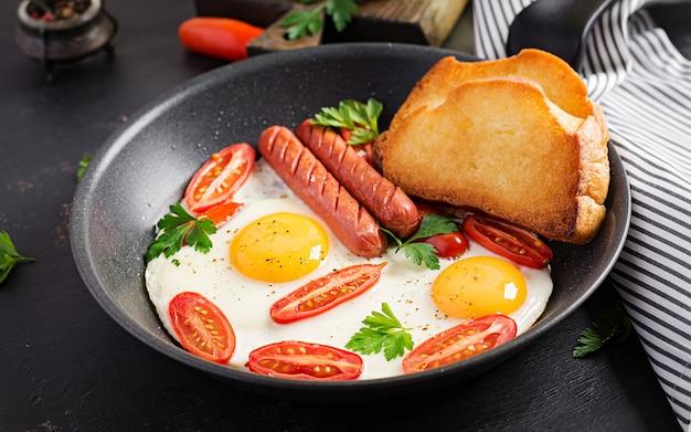 Desayuno inglés: huevo frito, tomates, salchichas y tostadas. vista superior