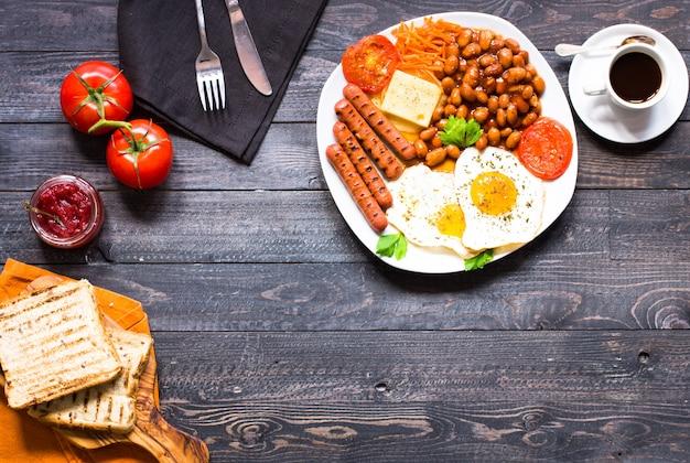 Desayuno inglés. huevos fritos salchichas frijoles tostadas de pan tomates queso sobre un fondo de madera