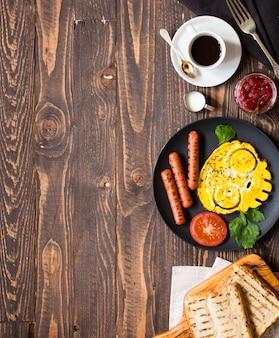 Desayuno inglés. huevos fritos, salchichas, frijoles, tostadas de pan, tomates, queso sobre madera.