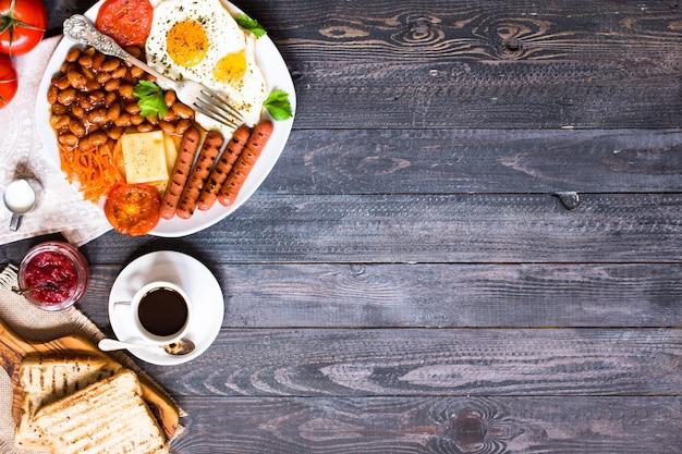 Desayuno inglés. huevos fritos, salchichas, frijoles, tostadas de pan, tomates, queso sobre una superficie de madera,