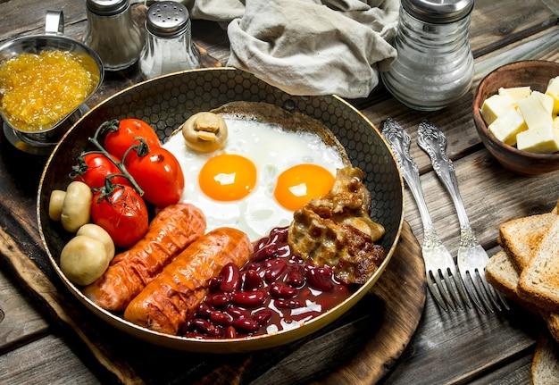 Desayuno inglés huevos fritos con salchichas, tocino y frijoles enlatados rojos sobre una mesa rústica.