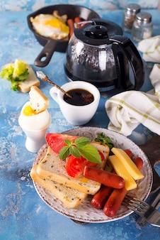 Desayuno inglés. huevos fritos, salchichas, tostadas, tomates en mesa de piedra.
