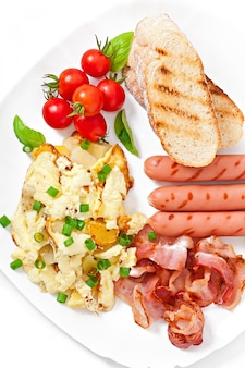Desayuno inglés con huevos revueltos, tocino, salchichas y tostadas.