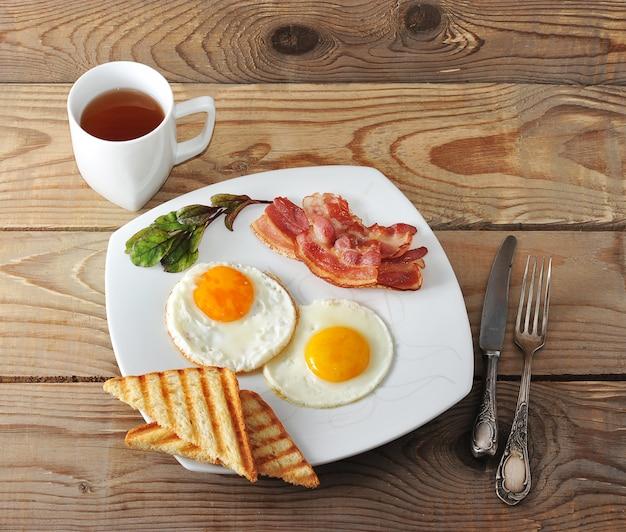 Desayuno inglés con huevos revueltos, tocino, tostadas fritas y té.
