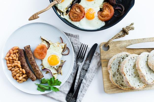Desayuno inglés en una placa gris en un fondo blanco.