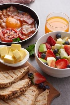 Desayuno inglés en sartén con huevos fritos, tocino, frijoles, tomates asados.