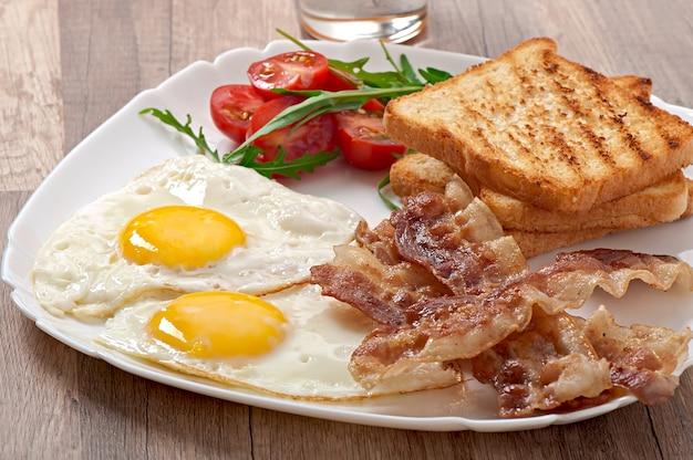 Desayuno inglés: tostadas, huevo, tocino y verduras.