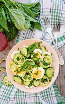Desayuno en el jardín de verano. ensalada de huevos y pepinos con cebolla verde y albahaca. vista superior. lay flat