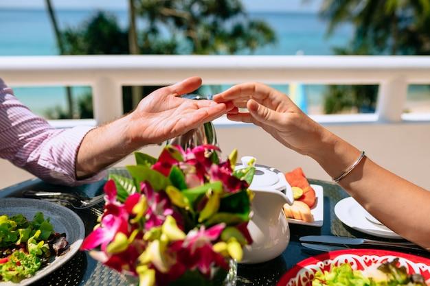 Desayuno una joven pareja en un complejo tropical cerca. un hombre toca la mano de una mujer. la mesa es un plato con frutas tropicales. vacaciones de verano en países cálidos.