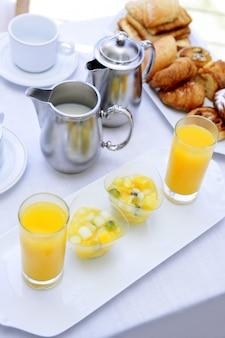 Desayuno con jugo de naranja café té leche.