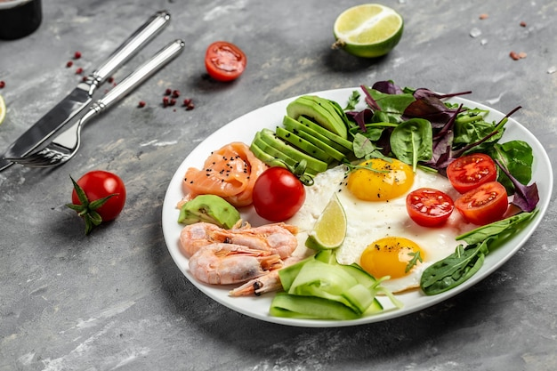 Desayuno keto con salmón, camarones cocidos, camarones, huevos fritos, ensalada fresca, tomates, pepinos y aguacate. concepto de alimentación saludable.