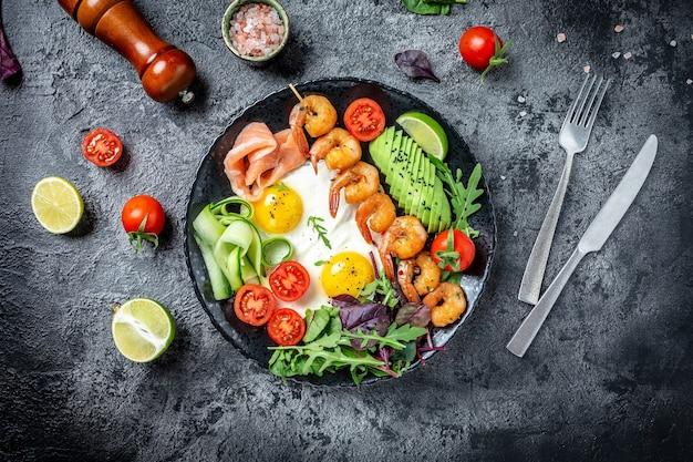 Desayuno keto salmón bajo en carbohidratos, camarones a la parrilla, camarones, huevos fritos, ensalada fresca, tomates, pepinos y aguacate. banner, lugar de receta de menú para texto, vista superior.