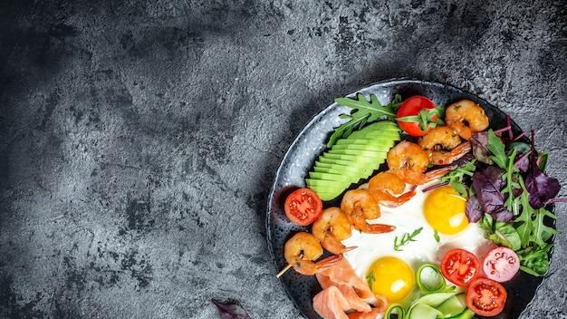 Desayuno keto salmón bajo en carbohidratos, camarones a la parrilla, camarones, huevos fritos, ensalada fresca, tomates, pepinos y aguacate. formato de banner largo, vista superior.
