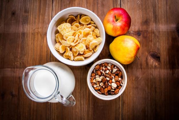 Desayuno ligero y saludable. copos de maíz, leche, manzanas y nueces para ellos.