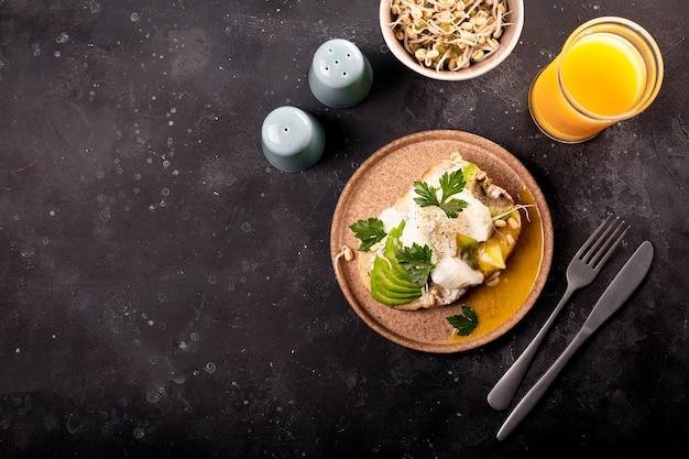 Desayuno ligero de verano: sándwich con aguacate, requesón, frijoles germinados y huevo escalfado con jugo de naranja.