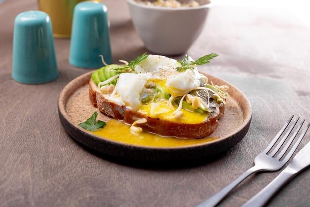 Desayuno ligero de verano - sándwich con aguacate, requesón, frijoles germinados y huevo escalfado en la mesa de cerca.