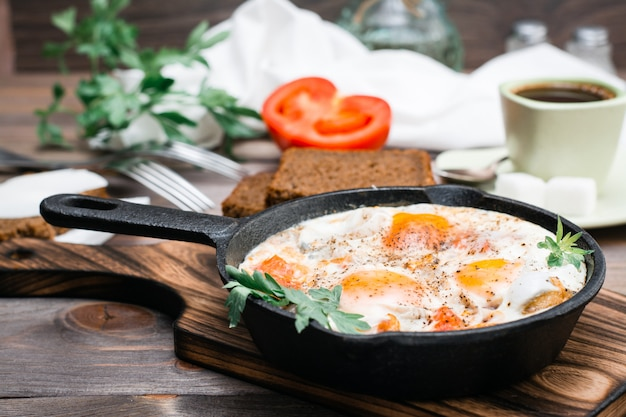 Desayuno listo para comer: shakshuka de huevos fritos con tomate y perejil en una sartén, pan con mantequilla y café en una mesa de madera