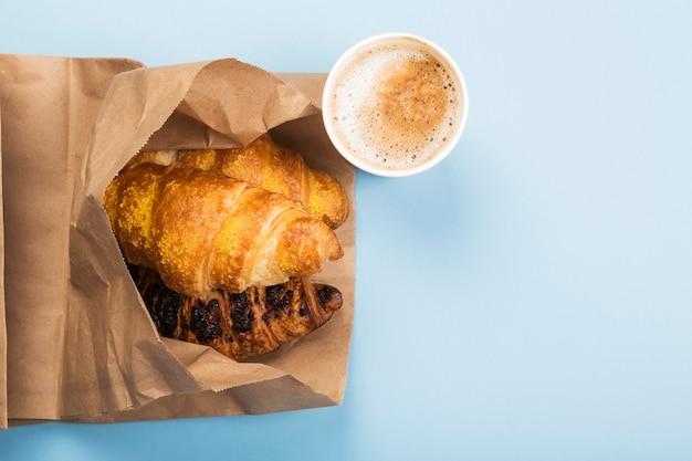 Desayuno para llevar - cruasanes y café con leche en el espacio azul. entrega de productos. vista superior, espacio de copia
