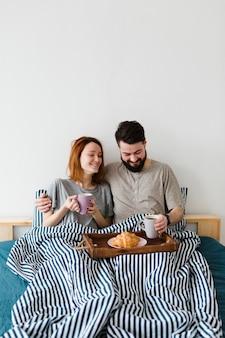 Desayuno de la mañana en la cama y pareja sonriente