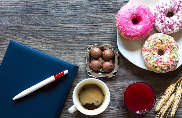Desayuno por la mañana con donas de colores y café.