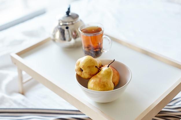 Desayuno por la mañana pan y mantequilla, té y pera.