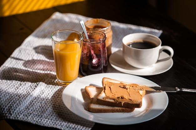 Desayuno con mantequilla de maní y mermelada y una taza de café en una mesa de madera en el sol de la mañana