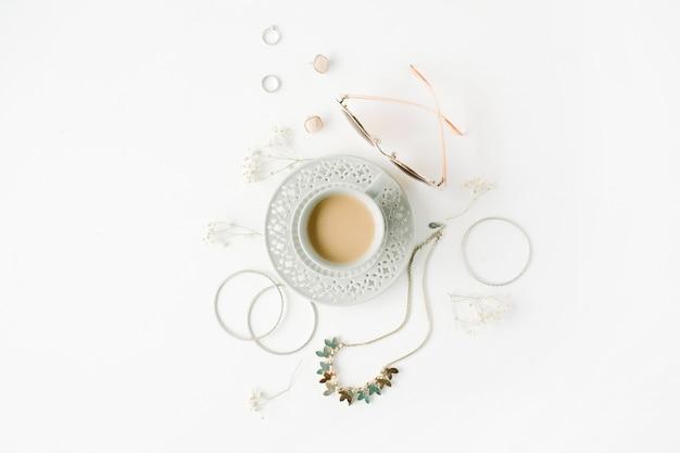 Desayuno matutino con taza de café con leche y arreglo de accesorios de moda en blanco