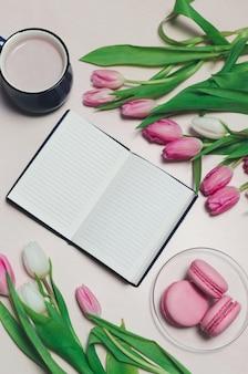 Desayuno en la mesa. composición plana con flores, un bloc de notas una taza de café y dulces de fondo