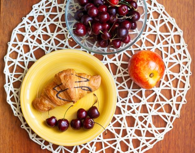 Desayuno en la mesa, croissant en un plato, cerezas en un bol y un melocotón, vista superior