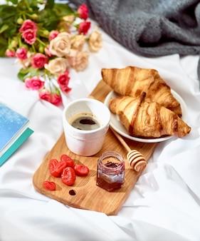 Desayuno en una mesa de madera y flores.