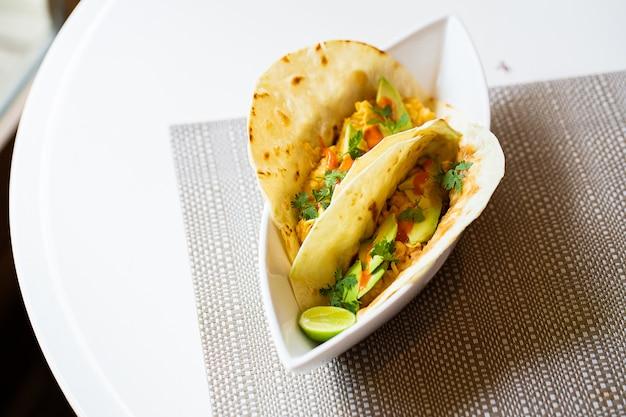 Desayuno mexicano de un taco de desayuno. lados de pico de gallo, aguacate, lima y jalapeño.