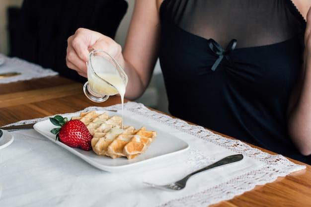 Desayuno de mujer de gofres con una mesa de café en la sala de estar