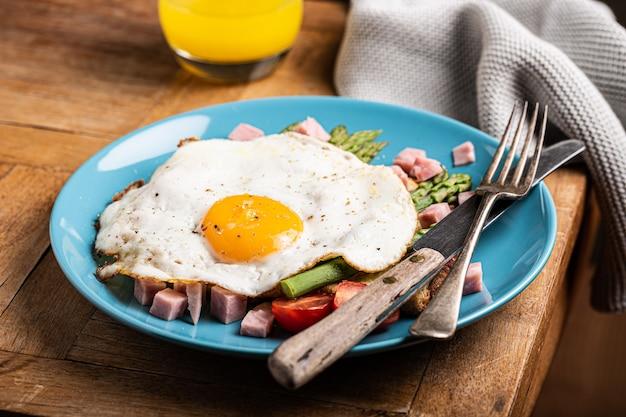 Desayuno o almuerzo saludable con huevo frito, tostadas de pan, espárragos verdes y tomates en placa azul sobre mesa de madera antigua