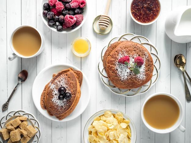 Desayuno de panqueques de chocolate con bayas, una taza de café con crema, miel y cereales.