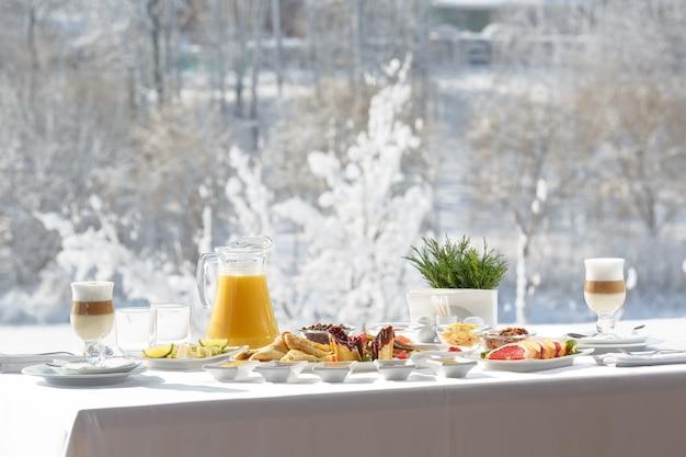 Desayuno de panqueques de invierno en la terraza afuera del restaurante en el fondo de nieve panqueques, fruta, jugo y café