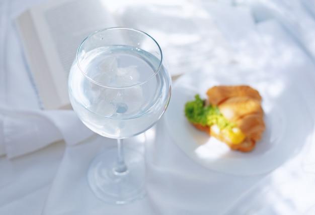 Desayuno perfecto vaso de agua, croissant y libro