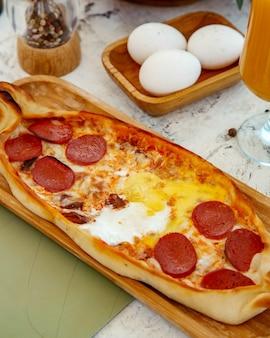 Desayuno pide con pepperoni, queso y huevos.