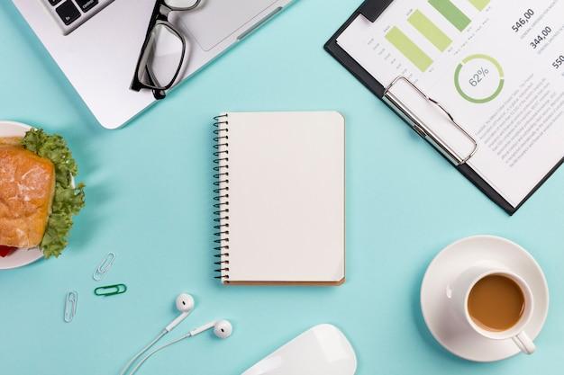 Desayuno, plan de negocios, computadora portátil, anteojos, bloc de notas en espiral, auriculares y mouse en el escritorio azul de la oficina