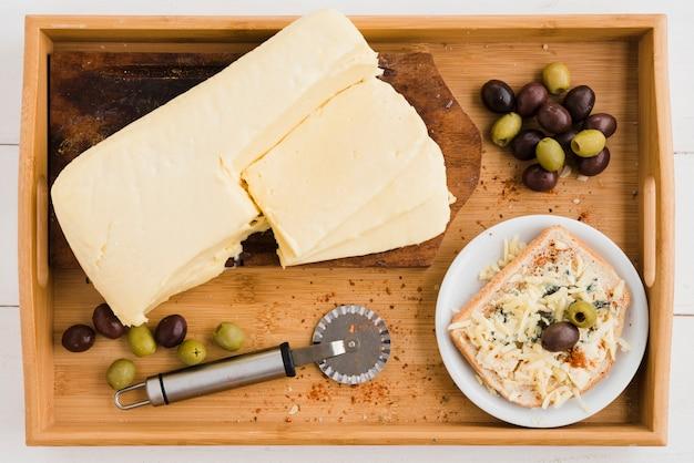 Desayuno de queso rallado con aceitunas en pan en bandeja de madera.