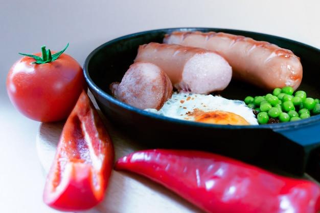 Un desayuno rápido de huevos revueltos y salchichas. y también guisantes pimiento y tomate.