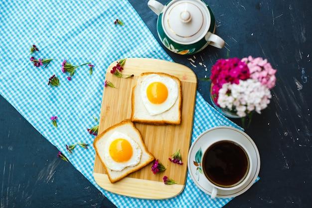 Desayuno recién preparado con huevos fritos en forma de corazón y taza de té.