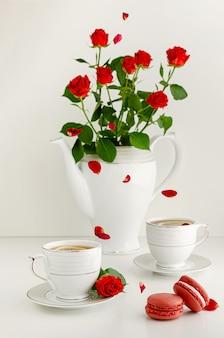 Desayuno romántico con té, macarons y ramo de rosas.