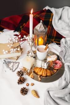 Desayuno con rosquillas, croissant, galletas y taza de té en una bandeja en la cama