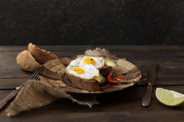 Desayuno rural tostadas con huevos fritos y aguacate sobre tabla de madera