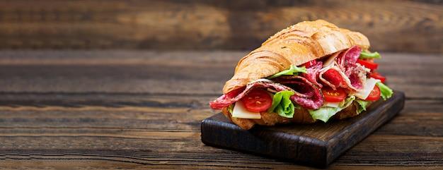 Desayuno sabroso croissant apetitoso con salami y queso y tomates