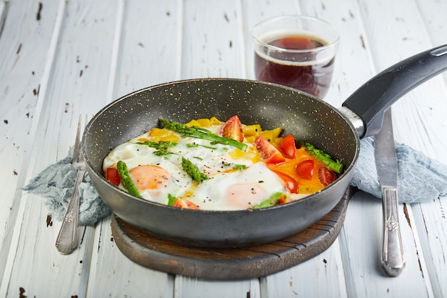 Desayuno sabroso huevos fritos en una sartén con café