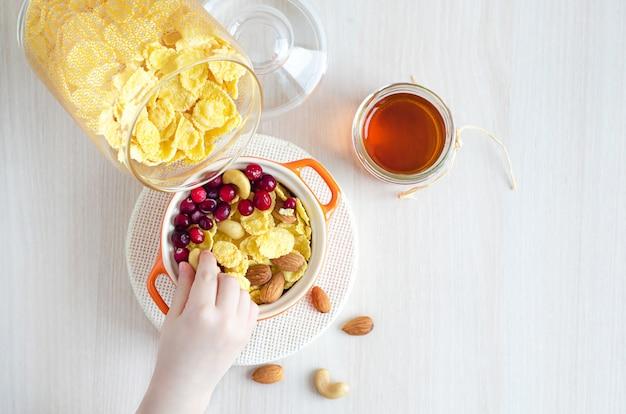 Desayuno sabroso y saludable. copos de maíz cubiertos con bayas, nueces, miel. mano de niños y comida.