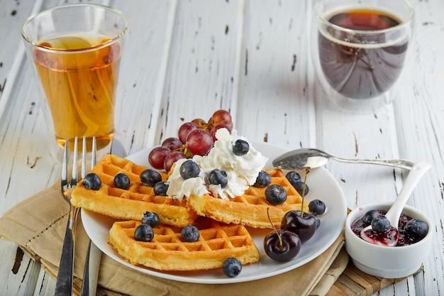 Desayuno sabroso waffles belgas con crema batida de arándanos y mermelada sobre un blanco de madera